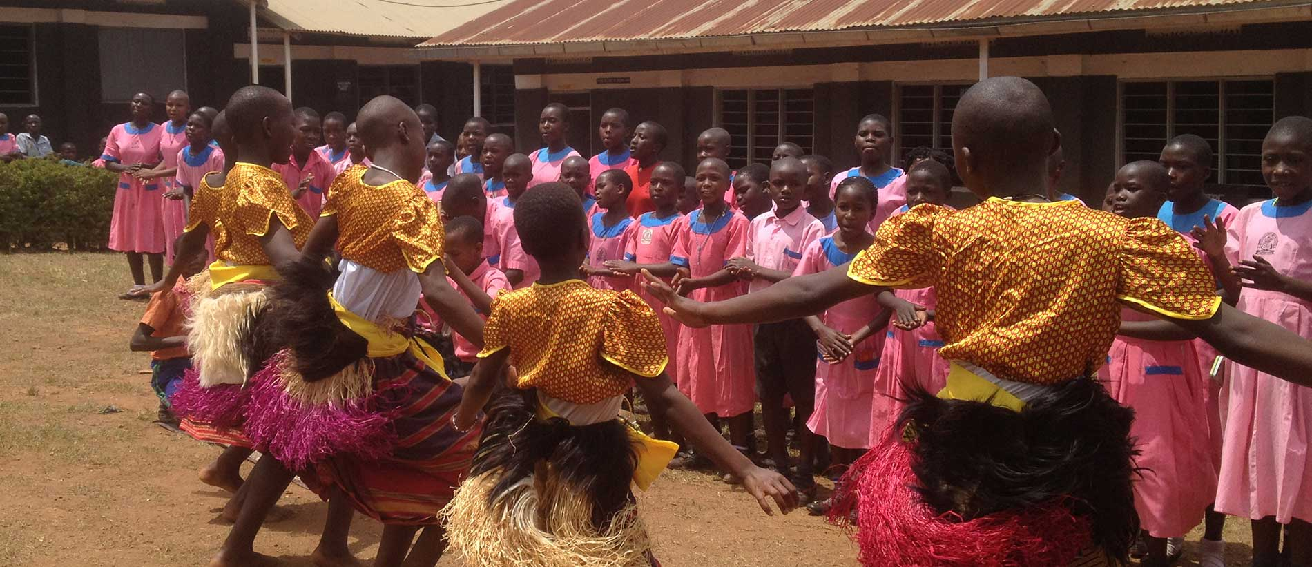 Children perform a traditional dance at Little Flowers Primary School Kalisizo, Uganda
