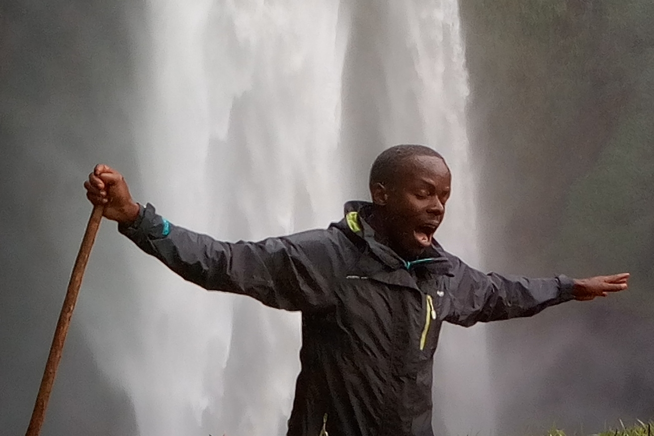Man stands under the Sipi Falls in Uganda and enjoys the splashes from the water